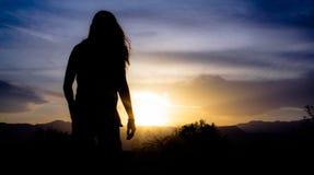 Silueta de la mujer en la puesta del sol Fotografía de archivo