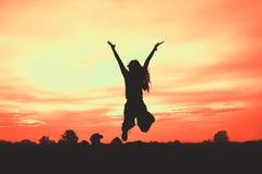 Silueta de la mujer en la puesta del sol, salto de la mujer, Fotografía de archivo