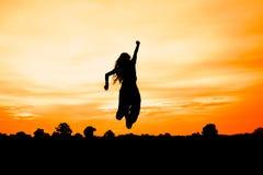 Silueta de la mujer en la puesta del sol, salto de la mujer, Imágenes de archivo libres de regalías