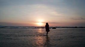 Silueta de la mujer en la playa en la puesta del sol hermosa almacen de video