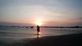 Silueta de la mujer en la playa en la puesta del sol hermosa metrajes