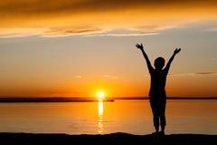 Silueta de la mujer en la puesta del sol de oro con el espacio de la copia Foto de archivo