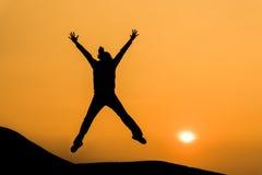 Silueta de la mujer en salto feliz en el cielo anaranjado de la puesta del sol Foto de archivo