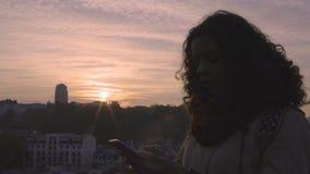 Silueta de la mujer feliz joven que manda un SMS en smartphone en la puesta del sol, relación metrajes