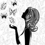 Silueta de la mujer joven con las mariposas del vuelo Fotografía de archivo