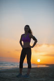 Silueta de la mujer joven de la aptitud que se coloca en la playa en la oscuridad Fotos de archivo libres de regalías