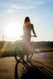 Silueta de la mujer joven de la bicicleta Imagenes de archivo