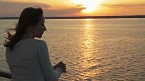 Silueta de la mujer joven en el barco de cruceros en la puesta del sol metrajes