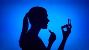 Silueta de la mujer joven que aplica el lápiz labial Cara femenina del ` s en perfil con el espejo en fondo azul almacen de metraje de vídeo