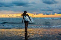 Silueta de la mujer joven que camina a lo largo de la playa en la puesta del sol Imagen de archivo