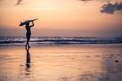 Silueta de la mujer joven que camina a lo largo de la playa en la puesta del sol Fotos de archivo libres de regalías