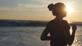 Silueta de la mujer joven que corre en la playa del mar en la puesta del sol Muchacha que activa a lo largo de orilla del océano  foto de archivo