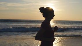 Silueta de la mujer joven que corre en la playa del mar en la puesta del sol Muchacha que activa a lo largo de orilla del océano  Foto de archivo libre de regalías