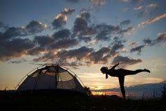 Silueta de la mujer joven que estira encima de las montañas en acampar cercano de la puesta del sol contra el cielo hermoso imágenes de archivo libres de regalías