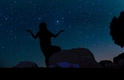 Silueta de la mujer joven que hace práctica de la yoga en la colina de la arena debajo de las estrellas, Foto de archivo