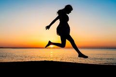 Silueta de la mujer joven que salta en la playa Fotos de archivo libres de regalías