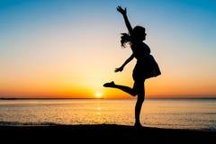 Silueta de la mujer joven que salta en la playa fotografía de archivo