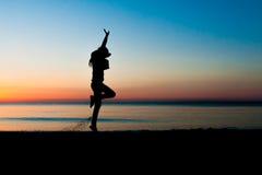 Silueta de la mujer joven que salta en la playa Fotografía de archivo libre de regalías