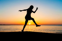 Silueta de la mujer joven que salta en la playa Foto de archivo
