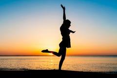 Silueta de la mujer joven que salta en la playa Imagen de archivo libre de regalías