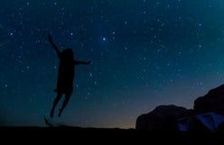 Silueta de la mujer joven que salta sobre la colina de la arena, debajo de la estrella Fotografía de archivo libre de regalías