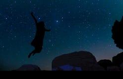 Silueta de la mujer joven que salta sobre la colina de la arena, debajo de la estrella Imágenes de archivo libres de regalías