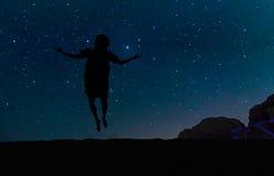 Silueta de la mujer joven que salta sobre la colina de la arena, debajo de las estrellas, de la vía láctea y de muchas estrellas  Fotos de archivo libres de regalías