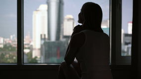 Silueta de la mujer joven que se sienta en cama y que mira fuera de ventana Paisaje de los rascacielos de la ciudad afuera metrajes