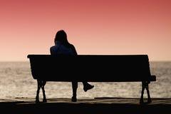 Silueta de la mujer joven que se sienta solamente en el banco imagen de archivo
