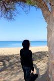 Silueta de la mujer que camina en la playa con la guitarra en capilla negra fotos de archivo