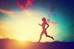 Silueta de la mujer que corre en la puesta del sol Fotografía de archivo