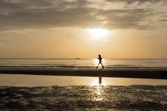 Silueta de la mujer que hace caminar enérgico en la playa en la puesta del sol fotografía de archivo