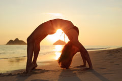 Silueta de la mujer que hace yoga imagenes de archivo