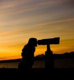 Silueta de la mujer que mira a través del telescopio Imágenes de archivo libres de regalías