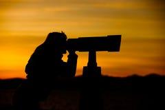 Silueta de la mujer que mira a través del telescopio Imagen de archivo libre de regalías
