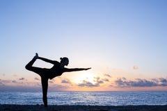 Silueta de la mujer que practica yoga auténtica en la playa en la puesta del sol fotografía de archivo libre de regalías