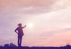 Silueta de la mujer que ruega sobre el cielo hermoso Imagen de archivo