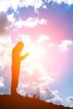Silueta de la mujer que ruega sobre fondo hermoso de la salida del sol Fotos de archivo