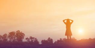 Silueta de la mujer que ruega sobre fondo hermoso del cielo Fotos de archivo libres de regalías