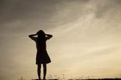 Silueta de la mujer que ruega sobre fondo hermoso del cielo Imágenes de archivo libres de regalías