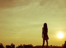 Silueta de la mujer que ruega sobre fondo hermoso del cielo Foto de archivo libre de regalías