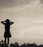Silueta de la mujer que ruega sobre fondo hermoso del cielo Imagen de archivo
