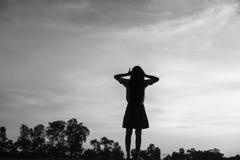 Silueta de la mujer que ruega sobre fondo hermoso del cielo Foto de archivo