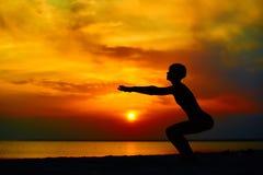 Silueta de la mujer que se coloca en la actitud de la yoga en la playa durante una puesta del sol asombrosa imagen de archivo libre de regalías