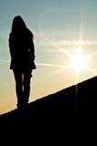 Silueta de la mujer que se coloca en una pared en puesta del sol hermosa Fotografía de archivo