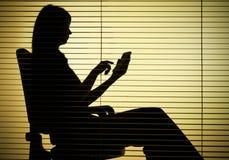 Silueta de la mujer que se sienta con la calculadora (persianas) imagen de archivo
