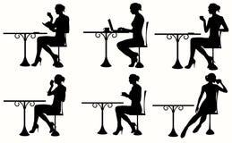 Silueta de la mujer que se sienta en la tabla Imágenes de archivo libres de regalías
