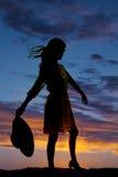 Silueta de la mujer que sostiene el viento trasero del sombrero Imagen de archivo