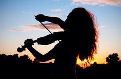 Silueta de la mujer que toca el violín Fotos de archivo libres de regalías