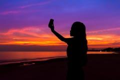 Silueta de la mujer que toma la foto de la puesta del sol con el teléfono móvil, en imagen de archivo libre de regalías
